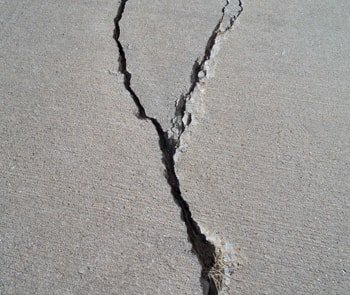 Photo of cement slab with Y shaped crack running through the middle vertically.