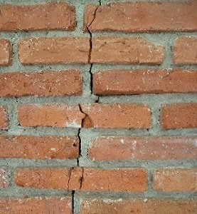 Photo of a red brick wall with a crack running vertically through the center