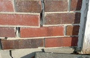 Photo of red brick wall with a zig zag crack up the side