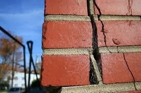 Photo of a building or house with red brick walls and a crack through the bricks.