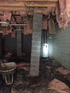 Photo of leaning cinderblock post in basement; water damaged basement insulation falling down