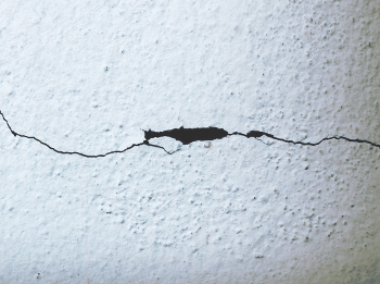 closeup of horizontal wall crack and chipping drywall in interior wall cracks